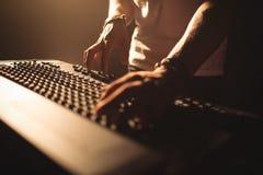 操作混音器的DJ在有启发性夜总会 库存图片