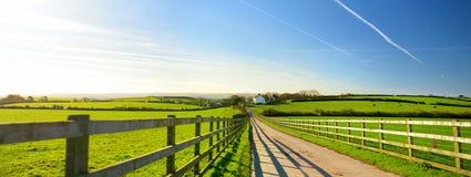 操刀在导致在风景康沃尔领域之间的小屋的路的铸件阴影在蓝天,康沃尔郡,英国下 免版税库存图片