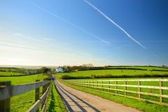 操刀在导致在风景康沃尔领域之间的小屋的路的铸件阴影在蓝天,康沃尔郡,英国下 库存图片