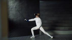 操刀锻炼使用VR耳机和训练模拟器竞争比赛的被集中的击剑者妇女实践户内 库存照片