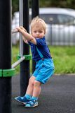 操场佩带的短裤和悬挂装置的小孩男孩 免版税库存照片