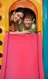 操场微笑的母亲和儿子 免版税库存照片