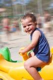 操场的愉快的孩子一个摇马的 免版税库存照片