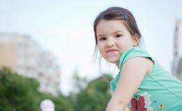 操场的愉快的微笑的小女孩 库存照片