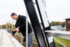 操练木屋顶的年轻木匠在建造场所 免版税库存照片
