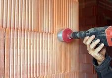 操练在墙壁的一个孔,一个人在工作 免版税库存照片