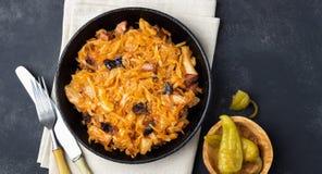 擦亮剂烹调-从新鲜的圆白菜、肉和修剪的Bigos传统盘  免版税库存照片