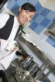 擦亮女服务员的刀叉餐具 免版税库存照片