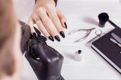 擦亮沙龙的秀丽nailfile钉子 在黑手套的主要制造的黑修指甲 奶油被装载的饼干 沙龙 免版税库存图片