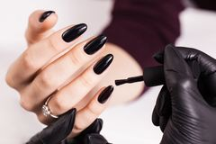 擦亮沙龙的秀丽nailfile钉子 在黑手套的主要制造的黑修指甲 免版税库存照片