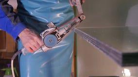 擦亮的玻璃的特别机器 研的玻璃 雇员手工擦亮的玻璃 研的特别设备和 免版税库存图片