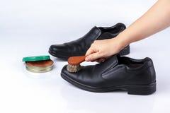 擦亮黑皮鞋的妇女的手 免版税库存照片