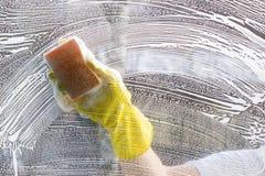 擦净剂洗涤在洗碗布之外的一个窗口 免版税库存图片