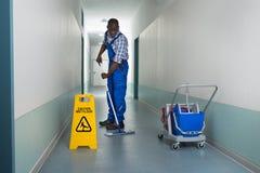 擦在走廊的男性管理员 免版税库存图片