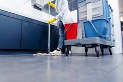 擦地板的清洁女工低射击在休息室 免版税库存照片