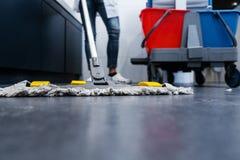 擦地板的清洁女工低射击在休息室 库存图片