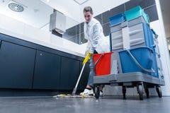 擦地板的清洁女工在休息室 免版税库存照片