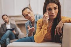 擦她的泪花的被注重的妇女在精神分析的会议期间 库存图片