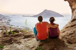 攀岩运动员夫妇有休息,当坐在底层峭壁和享受泰伦佐斯岛海岛美丽如画的看法在前面时 库存照片
