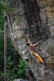 攀岩运动员,登高上面 上升在自然岩石墙壁上的成功 库存照片