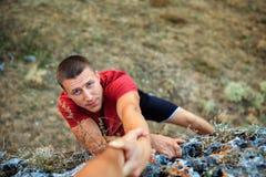 攀岩运动员给帮助的手伙伴 库存照片
