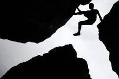 攀岩,在三岩石之间的人攀登在峭壁 免版税库存照片