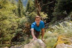 攀登一个岩石的独自的男人在森林里 库存图片