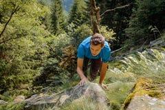攀登一个岩石的独自的男人在森林里 免版税库存图片
