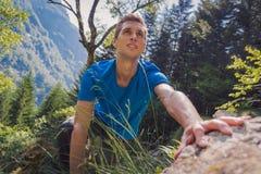 攀登一个岩石的独自的男人在森林里 免版税库存照片