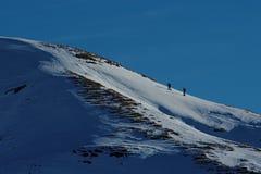 攀登一座多雪的山的土坎的人们用与雪靴或滑雪的意大利语Alpes, 免版税库存图片