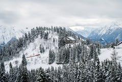 攀登一座多雪的山的火车 库存图片