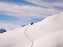 攀登一座山的两个backcountry滑雪者在瑞士阿尔卑斯在一个新雪秋天以后 库存图片