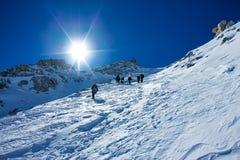 攀登与雪原的被栓的登山人山栓与与冰斧和盔甲的一条绳索 免版税库存图片