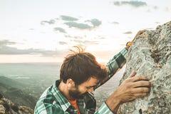 攀登在山的登山人一个岩石在日落 攀登岩石的远足者 库存图片