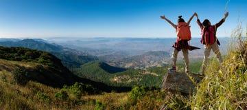 攀登山峭壁的两个女性徒步旅行者 免版税库存图片