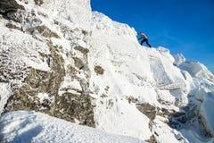攀登山顶面的登山家盖用冰和雪,努力去做在岩石峰顶的人远足者  时数横向季节冬天 免版税库存图片