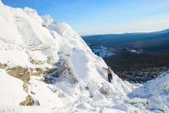 攀登山顶面的登山家盖用冰和雪,努力去做在岩石峰顶的人远足者  时数横向季节冬天 免版税图库摄影