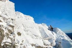 攀登山顶面的登山家盖用冰和雪,努力去做在岩石峰顶的人远足者  时数横向季节冬天 免版税库存照片