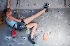 攀登岩石墙壁的青少年的女孩室内 图库摄影