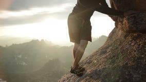 攀登岩石的一个人的腿在日落 股票录像