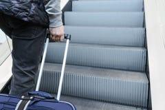 攀登带着一个手提箱的一个人的图象自动扶梯在他的手上: 免版税库存图片