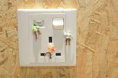 攀登电源插座的微型登山人 库存照片