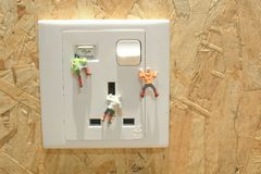 攀登电源插座的微型登山人 免版税库存图片