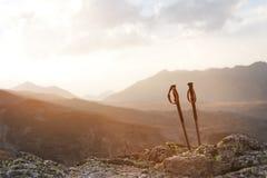 攀登的一座山专业棍子在一条高山道路的一块石头附近反对一朵蓝天和白色云彩  库存照片