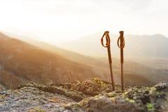 攀登的一座山专业棍子在一条高山道路的一块石头附近反对一朵蓝天和白色云彩  免版税库存图片