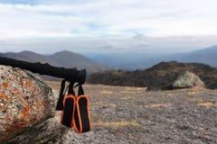 攀登的一座山专业棍子在一条高山道路的一块石头附近反对一朵蓝天和白色云彩 库存图片