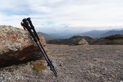 攀登的一座山专业棍子在一条高山道路的一块石头附近反对一朵蓝天和白色云彩 免版税库存照片
