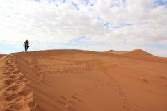 攀登一个沙丘的游人在Sossusvlei沙漠,纳米比亚 免版税图库摄影