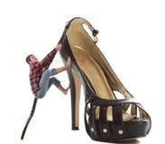 攀登一双巨大的鞋子的妇女 库存图片