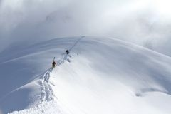 攀登一座多雪的山的滑雪者 图库摄影